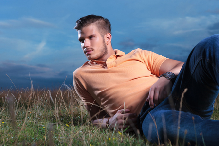 young casual man posing outdoor in the grass laying and looking away from the camera photo