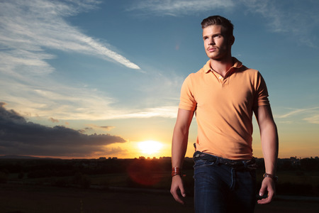 shirt: young casual man outdoor looking up, away from the camera, with the sunset behind him Stock Photo