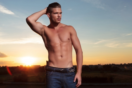 young topless man outdoor holding back his hair while looking away from the camera with the sunset behind photo