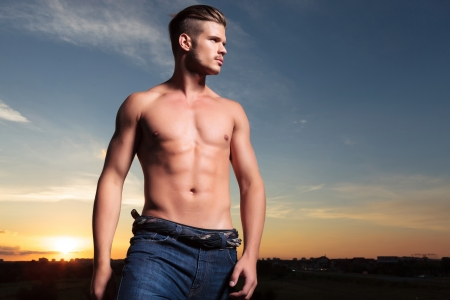 topless jeans: young topless man outdoor looking to his side, away from the camera with the sunset behind