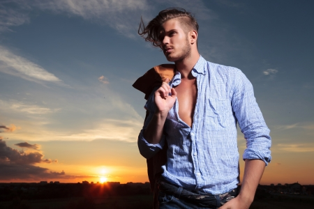casual young man standing with a hand in his pocket while the wind blows his hair and the sun sets behind him photo