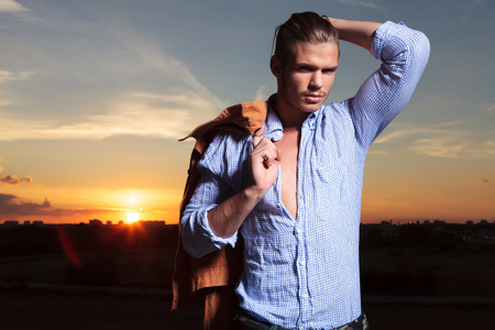 night shirt: casual young man standing outdoor and passing a hand through his hair while holding jacket over his shoulder and looking into the camera Stock Photo