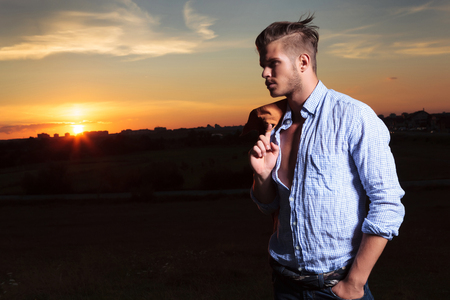 looking away from camera: casual young man standing outdoor with the sunset behind him while holding a hand in his pocket and looking away from the camera with his jacket on his shoulder