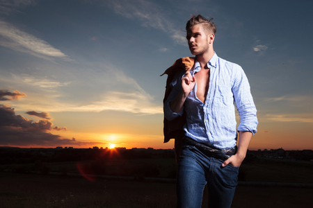 casual young man standing outdoor with a hand in his pocket and his jacket on his shoulder while looking away with the sunset behind photo