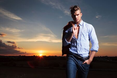 casual young man standing with a hand in his pocket outdoor during sunset photo