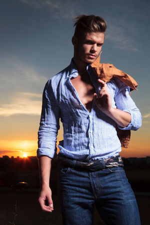 night shirt: casual young man standing outdoor with his jacket over his shoulder with the sunset behind him Stock Photo
