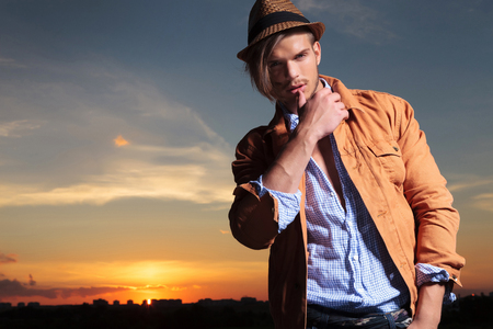 casual young man standing outdoor and looking down at the camera while touching his lower lip with his thumb and the sunset behind photo