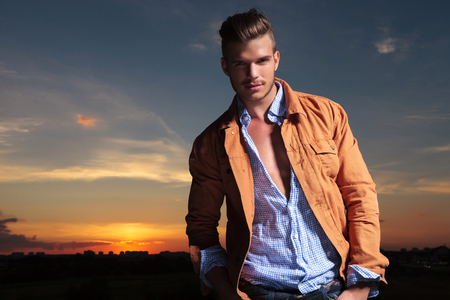 man behind: casual young man standing outdoor and smiling for the camera while with both hands in pockets and the sunset behind