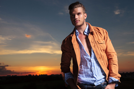 casual young man standing outdoor and looking up while holding both hands in his pockets with the sunset behind him photo