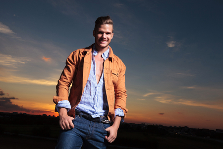 casual young man standing outdoor and holding both thumbs in his pockets while laughing at the camera with the sunset behind photo