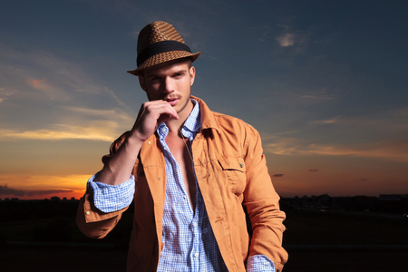 casual young man standing outdoor with a straw in his mouth and looking into the camera with the sunset behind him photo