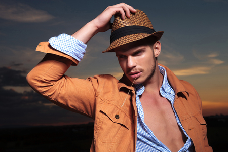 straw hat: casual young man standing outdoor with a hand on his hat and a straw in his mout while looking away from the camera with the sunset behind Stock Photo