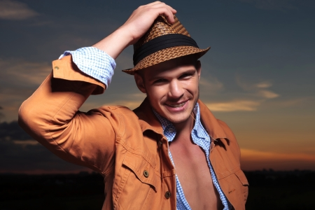 night shirt: casual young man standing outdoor with his hand on his hat while smiling for the camera with a straw in his mouth and the sunset behind
