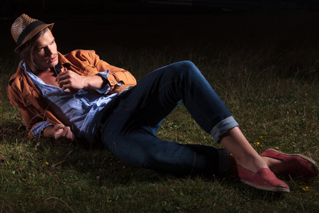 late summer: casual young man relaxing in the grass late in the night and holding a straw in his mouth while looking away from the camera Stock Photo