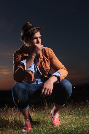 sitting on the ground: casual young man sitting outdoor crouched and holding a straw in his mouth while looking away from the camera Stock Photo
