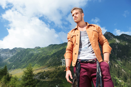 young casual man standing in the mountains, holding a hand in his pocket and looking away from the camera photo