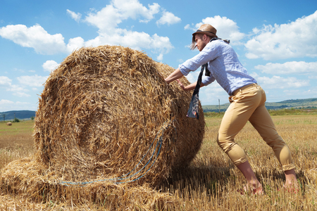 haystack: young casual man posing outdoor pushing a round haystack and looking away