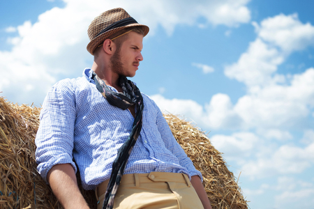 frowned: young casual man posing outdoor on a haystack while looking away with a frown and a straw behind his ear Stock Photo