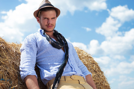 hands behind back: young casual man posing outdoor and looking into the camera while leaning on a haystack