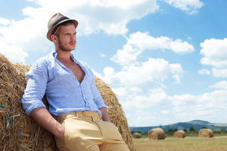 young casual man posing outdoor with both hands in pockets and looking away while leaning back on a haystack photo