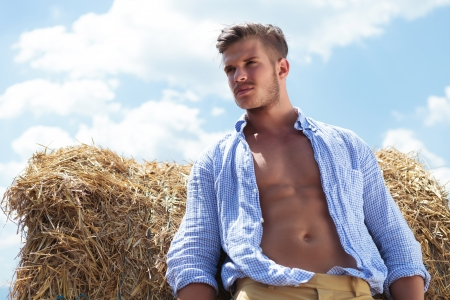 shirt unbuttoned: young casual man posing outdoor looking away with a haystack behind him and with his shirt unbuttoned Stock Photo