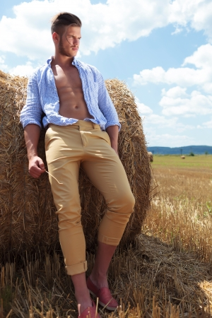 haystack: full length picture of a young casual man posing outdoor and looking away while leaning on a haystack with a straw in his hand