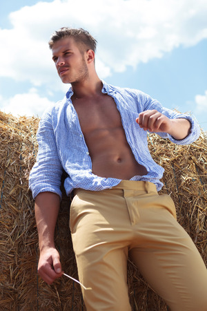 unbuttoned: young casual man posing outdoor with haystack behind and straw in hand, looking away from the camera