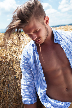 wind down: closeup of a young casual man posing outdoor with his hair in the wind and looking down, away from the camera with a haystack behind Stock Photo