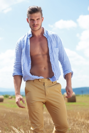 shirt unbuttoned: young casual man posing outdoor with opened shirt, looking into the camera