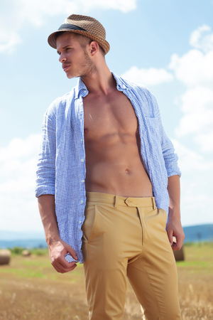 shirt unbuttoned: closeup portrait of a young casual man posing outdoor with his shirt unbuttoned while looking to his side, away from the camera Stock Photo