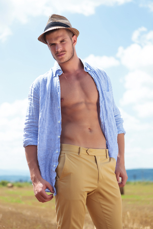 shirt unbuttoned: closeup photo of a young casual man posing outdoor with his shirt unbuttoned while looking into the camera