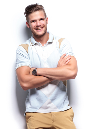 cute braces: young casual man laughing while holding his arms crossed. on white background Stock Photo
