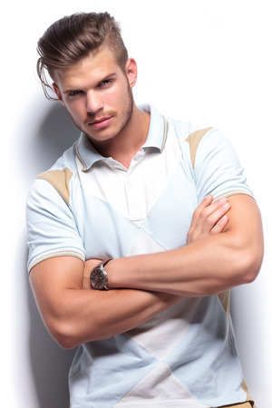 crossed arms: young fashion man holding his arms folded while looking at the camera. on a light background Stock Photo