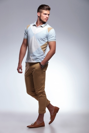 looking over shoulder: full length portrait of a young casual man standing with a hand in his pocket while looking over his shoulder. on gray background Stock Photo