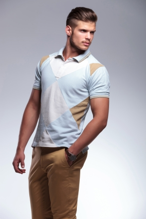 looking over shoulder: young casual man looking over his shoulder while holding a hand in his pocket. on gray background Stock Photo