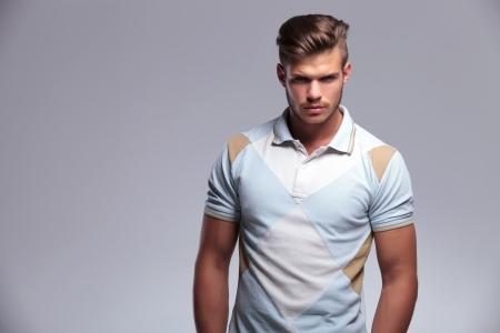 hombre: Primer plano de un joven casual mirando a la cámara. sobre fondo gris
