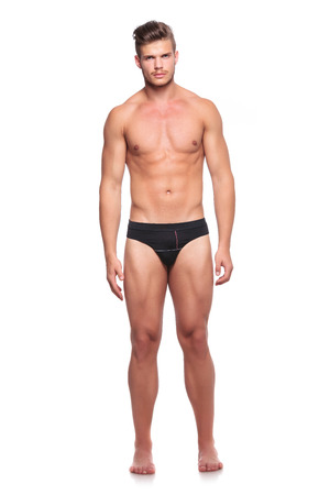 boy  naked: full length portrait of a young man wearing nothing but his underware and looking at the camera, isolated on white Stock Photo