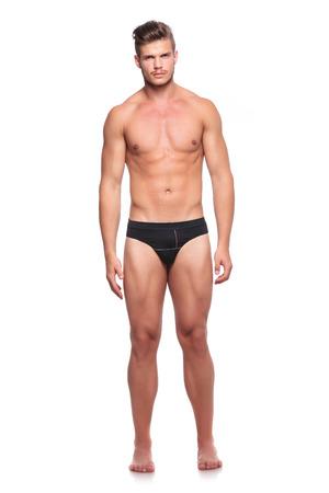 uomo nudo: ritratto a figura intera di un giovane uomo che indossa nulla, ma il suo underware e guardando la fotocamera, isolata su bianco