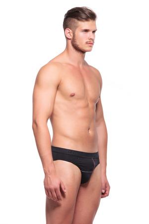 hombre desnudo: joven llevaba nada más que su underware y mirando a la cámara, aislado en blanco Foto de archivo