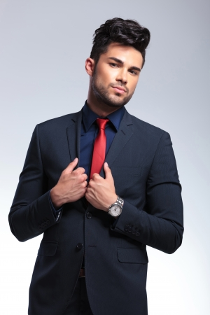 lapels: elegant young fashion man in tuxedo looking at the camera while holding his hands on the lapels of his jacket. on gray background
