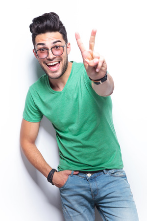 two boys: young casual man showing the victory gesture while smiling for the camera with a hand in his pocket. on white background