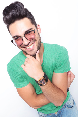 closeup portrait of a young casual man holding a hand at his chin and smiling for the camera. on white background photo