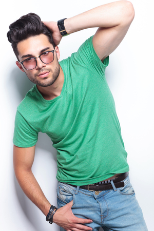 young casual man posing with a hand on the back of his head and a thumb in his pocket while looking into the camera. on white background photo