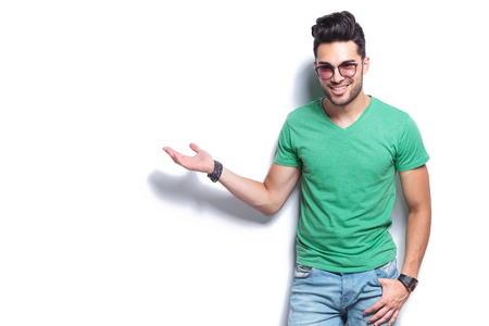 young casual man presenting something with a smile on his face an a thumb in his pocket. on white background photo