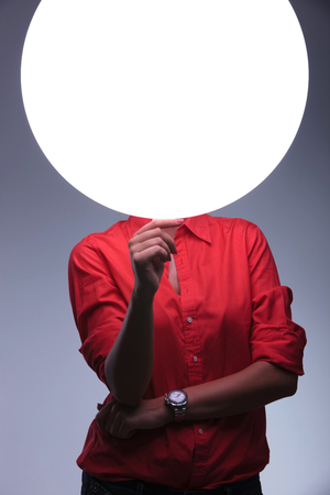 young casual woman holding a blank shiny circle in front of her face. on gray background photo
