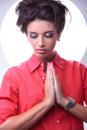 young casual woman praying and looking down while aura shines around her head. on gray background photo