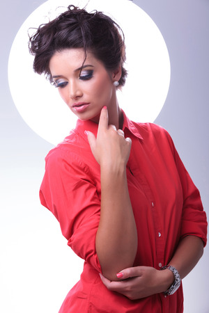 'young things': young casual woman looking down and touching her face with her finger while an aura shines behind her. on gray background