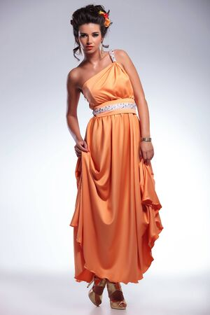 full length photo of a young fashion woman holding both hands on her dress and looking into the camera. on gray background Stock Photo