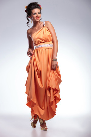 full length picture of a young fashion woman looking away from the camera while holding her long dress with both hands and smiling. on gray background