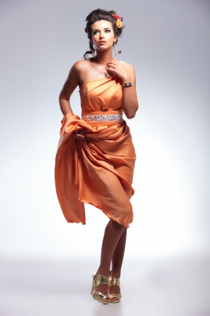 full length picture of a young fashion woman looking up,away from the camera while lifting her dress and revealing her legs. on gray background Stock Photo